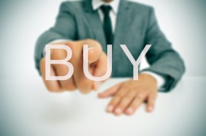 businessman sitting in a desk pointing the word buy written in the foreground
